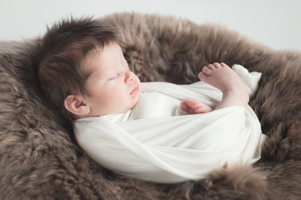 bébé emmailloté sur une peau douce