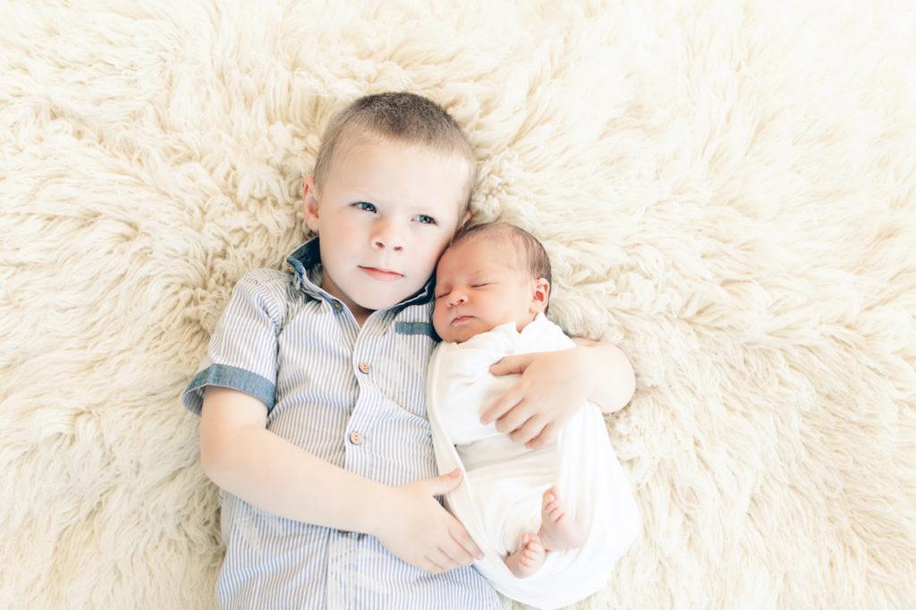 nouveau-né dans les bras de son frère